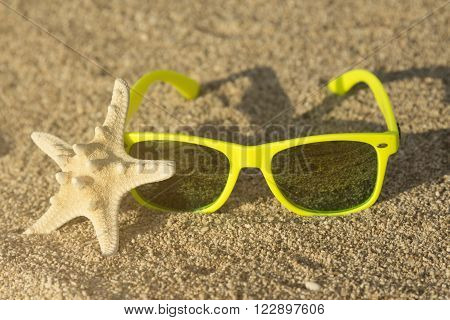 Sea star and garish green sunglasses on the sand at the sunset