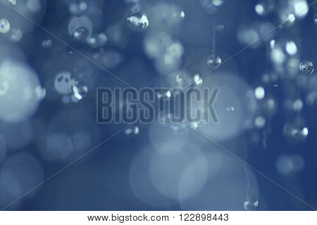 Falling water drops. Levitating rain drops. Abstract blue bokeh defocused background.