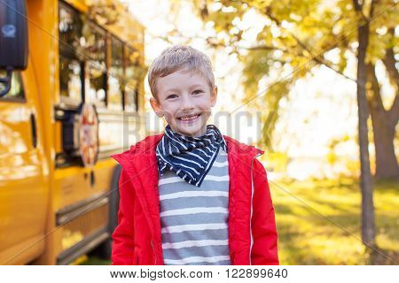 cheerful little boy standing near schoolbus ready to go to school back to school concept