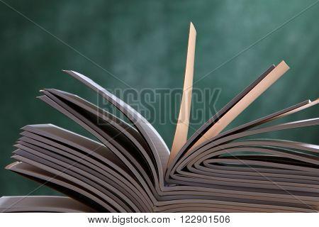 workbook on top of table in front of blackboard