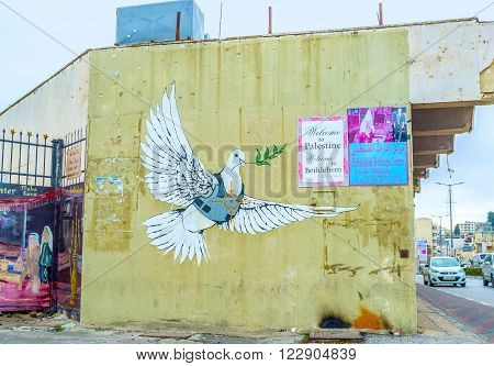 BETHLEHEM PALESTINE - FEBRUARY 18 2016: The mural of dove of peace dressed in a body armor with the aim on its heart painted on the wall of the house on February 18 in Bethlehem.