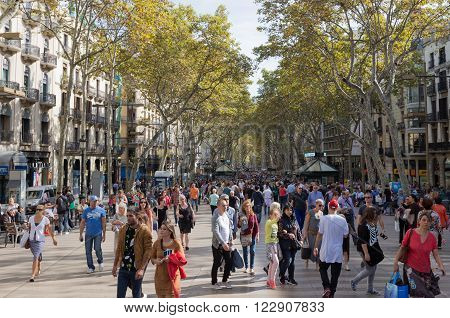 Barcelona - 10 October 2015: Many people and tourists stroll on the main tourist street of Barcelona in Catalonia - Rambla October 10 2015 Barcelona Spain