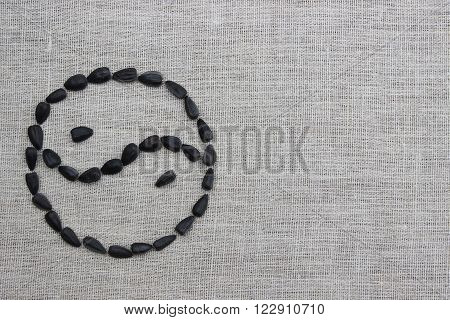 Yin yang symbol inlaid with sunflower seeds on a linen cloth