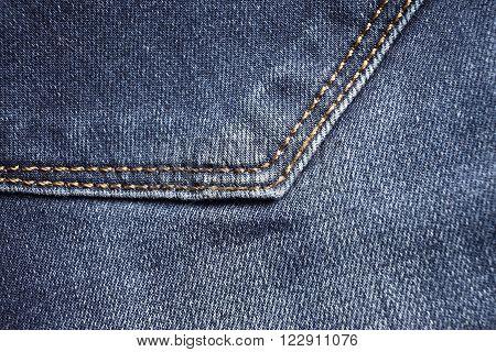 Blue jeans back pocket detail. Textile background
