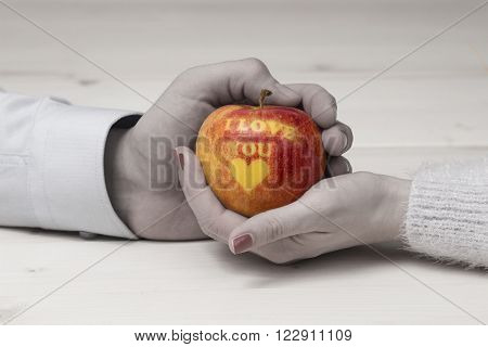 Male and female hand holding an apple with I love you inscription