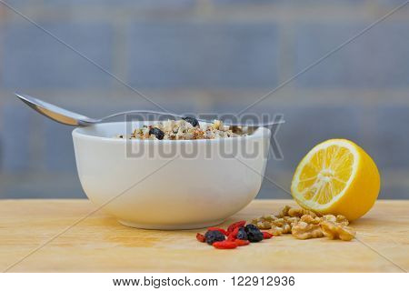 A bowl of delicious fresh quinoa and bulgar weat with parsley walnuts goji berries and blue berries sprinkled with olive oil and lemon juice ** Note: Shallow depth of field