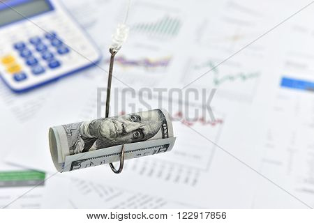 Rolled up scroll of US 100 dollar bill on a fishing hook. A concept of deceiving someone in several fields/market/trading i.e. financial currency forex stock equity bond derivatives shares etc