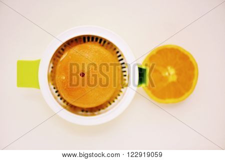 high-angle shot of an orange in a squeezer on an off-white table