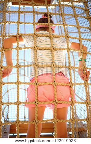 The girl standing inside the cable cell in playground, bottom view