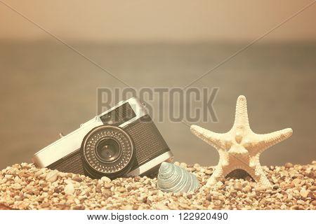 Retro camera, starfish and sea snail on pebble beach. Vacation symbols. Sea and horizon in the background.