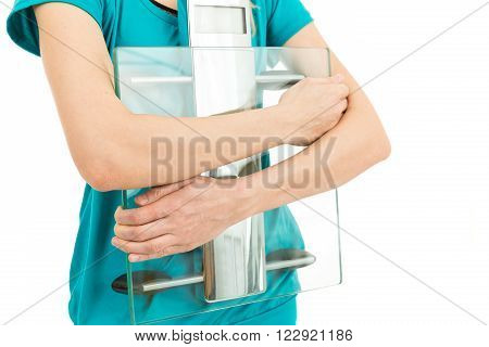 Close up of diet woman holding scale in her arms. Isolated on white background.
