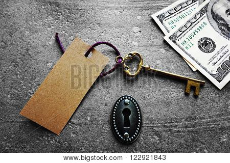 Antique key with paper tag and cash