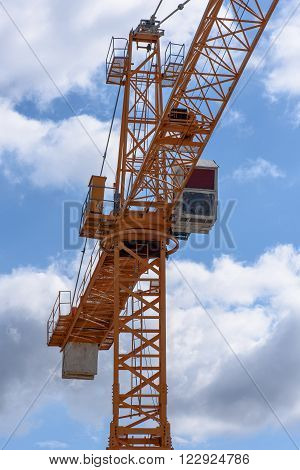 A yellow construction cranes above a cloudy sky.