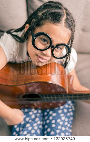 Happy Smiling Girl Learning To Play The Acoustic Guitar