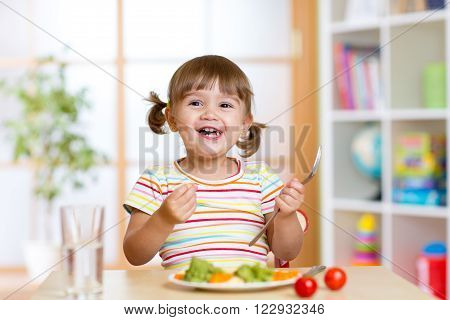 Happy kid girl eating vegetables. Healthy nutrition for children