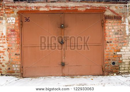 metal braun door of garage with lock. brick background poster