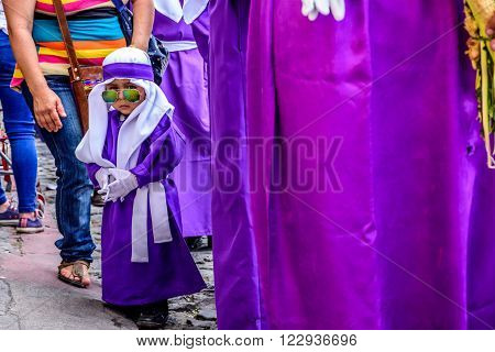 Antigua Guatemala - March 20 2016: Little boy wearing sunglasses & purple cucurucho outfit worn by penitent float bearers in Palm Sunday procession in colonial town with most famous Holy Week celebrations in Latin America.