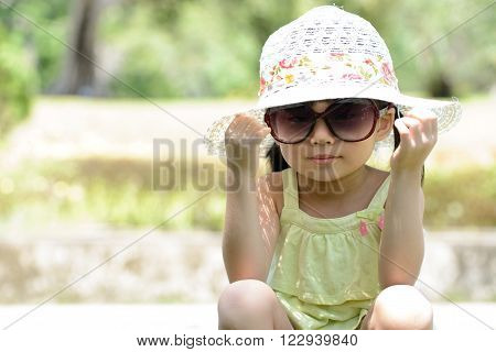 Little Asian girl wear sunglasses and floppy hat sitting in the park