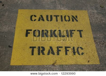 Caution forklift traffic text stenciled on concrete