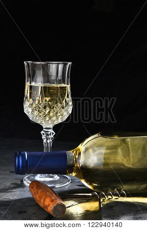 Closeup of a white wine bottle laying on its side on black slate. Vertical format with cork screw and wine glass, with copy space.