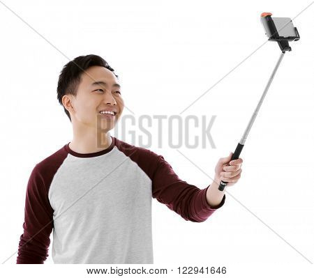 Young attractive man taking selfie with mobile phone isolated on white