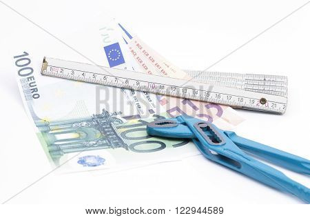 Image shows a yardstick with money and pliers isolated on white