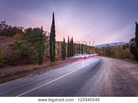 Mountain Road With Blurred Cars In Motion At Sunset