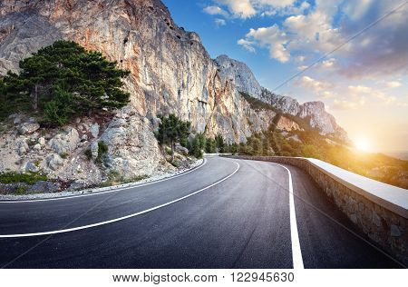 Winding Mountain Road With Rocks, Blue Sky At Sunset