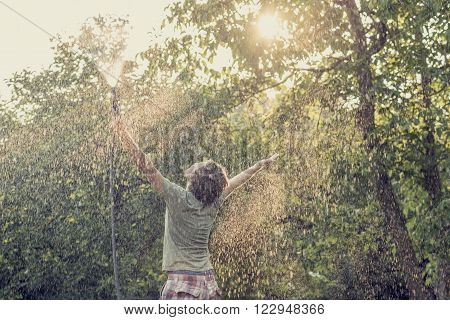 Young man outside in green summer nature holding garden hose spraying himself with arms lifted high in the air and bright sun lighting him through leaves of a tree toned retro effect.