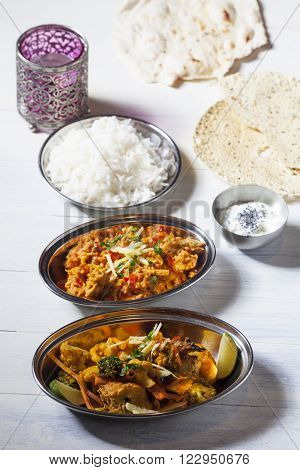 two indian dishes with rice on wood ** Note: Shallow depth of field