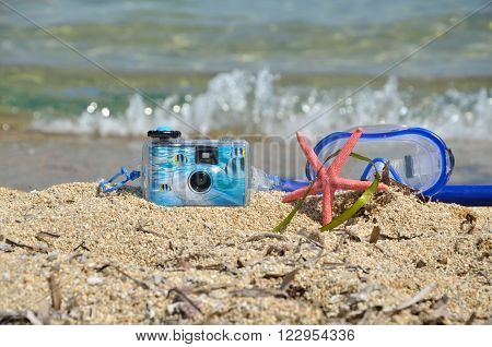 Water camera, snorkeling masque and sea star on sandy beach