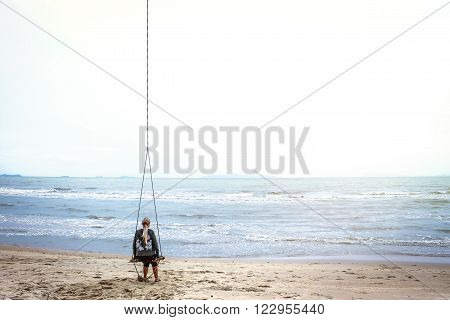 Single woman alone swinging and  looking into the distance over the horizon on a tropical beach with copy space. A bright sunlight illuminates the sea and the sky