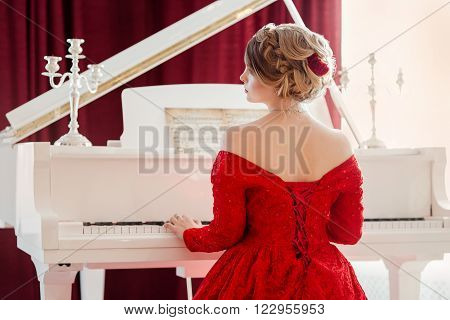 A young beautiful woman in a red evening dress sits at the grand piano