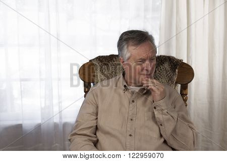 Elderly man struggling to remember something as he suffers from memory loss. Sitting in a rocking chair at home.