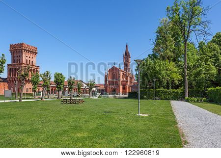 Small park, church and tower of University of Gastronomic Sciences in Pollenzo, Italy.