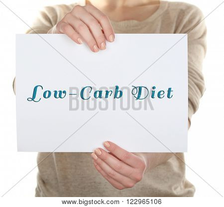 Woman holding card with text Low-Carb Diet, close-up