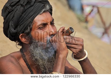 ALLAHABAD, INDIA - FEBRUARY 07, 2013: A unidentified sadhu is smoking ganja (marihuana) with chillum at the Kumbha Mela religious festival