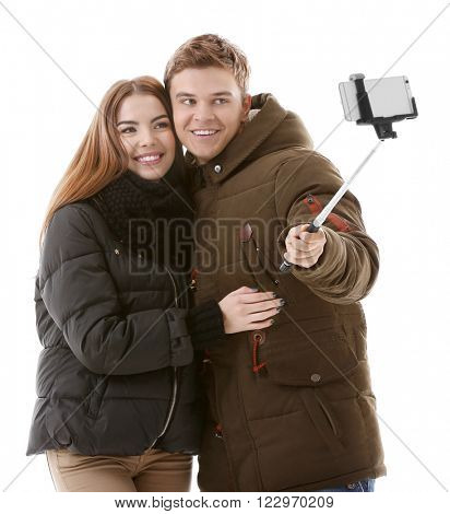 Teenager couple in winter clothing making photo by their self with mobile phone, isolated on white