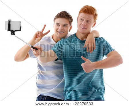 Two teenager boys making photo by their self with mobile phone, isolated on white