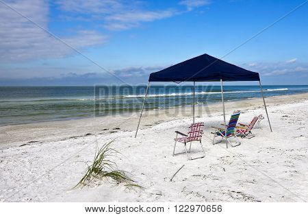 Portable Blue Canvass Shelter with Chairs Set up on the Beach