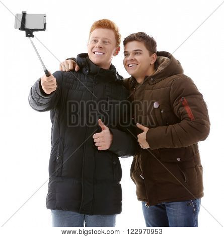 Two teenager boys in winter clothing making photo by their self with mobile phone, isolated on white
