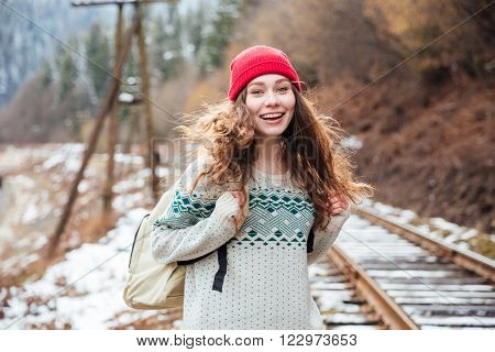 Smiling pretty young woman with backpack walking on railroad