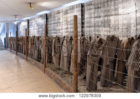 OSWIECIM POLAND - JULY 3 2009: Auschwitz I - Birkenau display in Block 15 of prisoners' striped uniforms and photos of victims