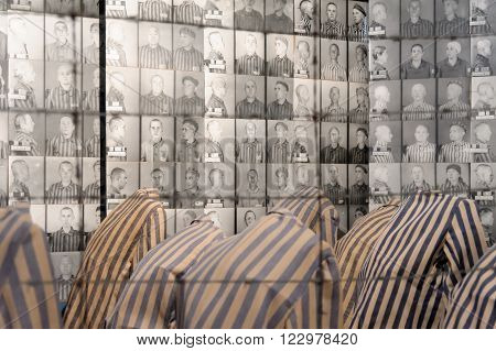 OSWIECIM, POLAND - JULY 3, 2009: Auschwitz I - Birkenau display in Block 15 of prisoners' striped uniforms and photos of victims