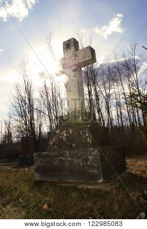 An old tombstone in a quiet gravesite with the sunshine backlighting the cross in a spirtual manner. ** Note: Visible grain at 100%, best at smaller sizes