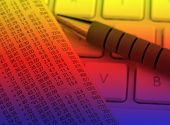 Financial newspaper resting on laptop keyboard with color lighting effect poster