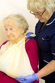 Nurse putting a senior ladies broken arm in a sling, showing obvious pain in ladies pale face poster