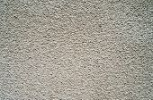 Detail of gray wall closeup uneven granular cement coating for use as a background poster