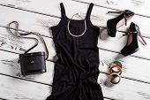 Black dress and small necklace. Jewelry and clothes on shelf. Frosted heel shoes and accessories. Suede shoes and retro purse. poster