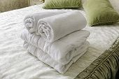 Towels in Hotel room. Closeup of hotel bedroom towels, selective focus. Welcome guests. Room service. White hotel towels rolled up at bed. poster